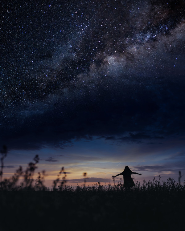 Art Photography Scene with woman dancing under milky way