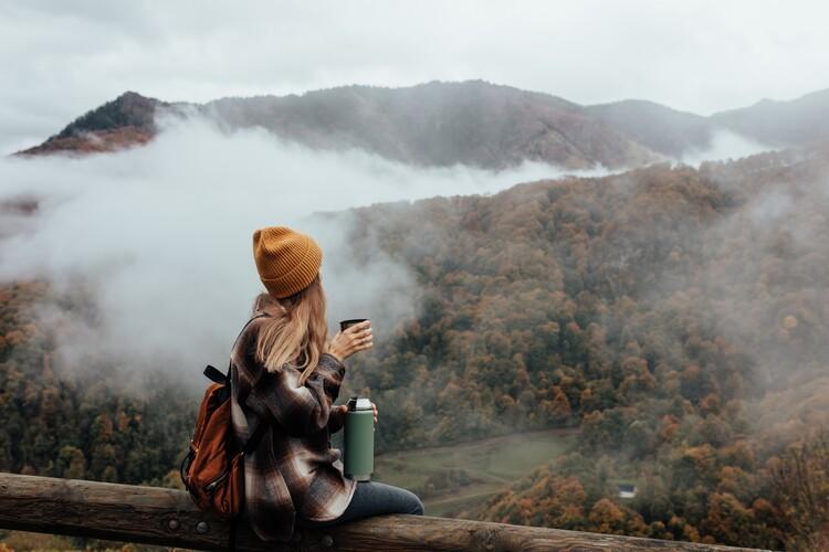 Eksklusiiviset taidevalokuvat Woman having breakfast in the mountains in autumn
