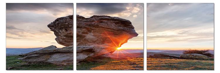 Sun setting behind a rock Mounted Art Print